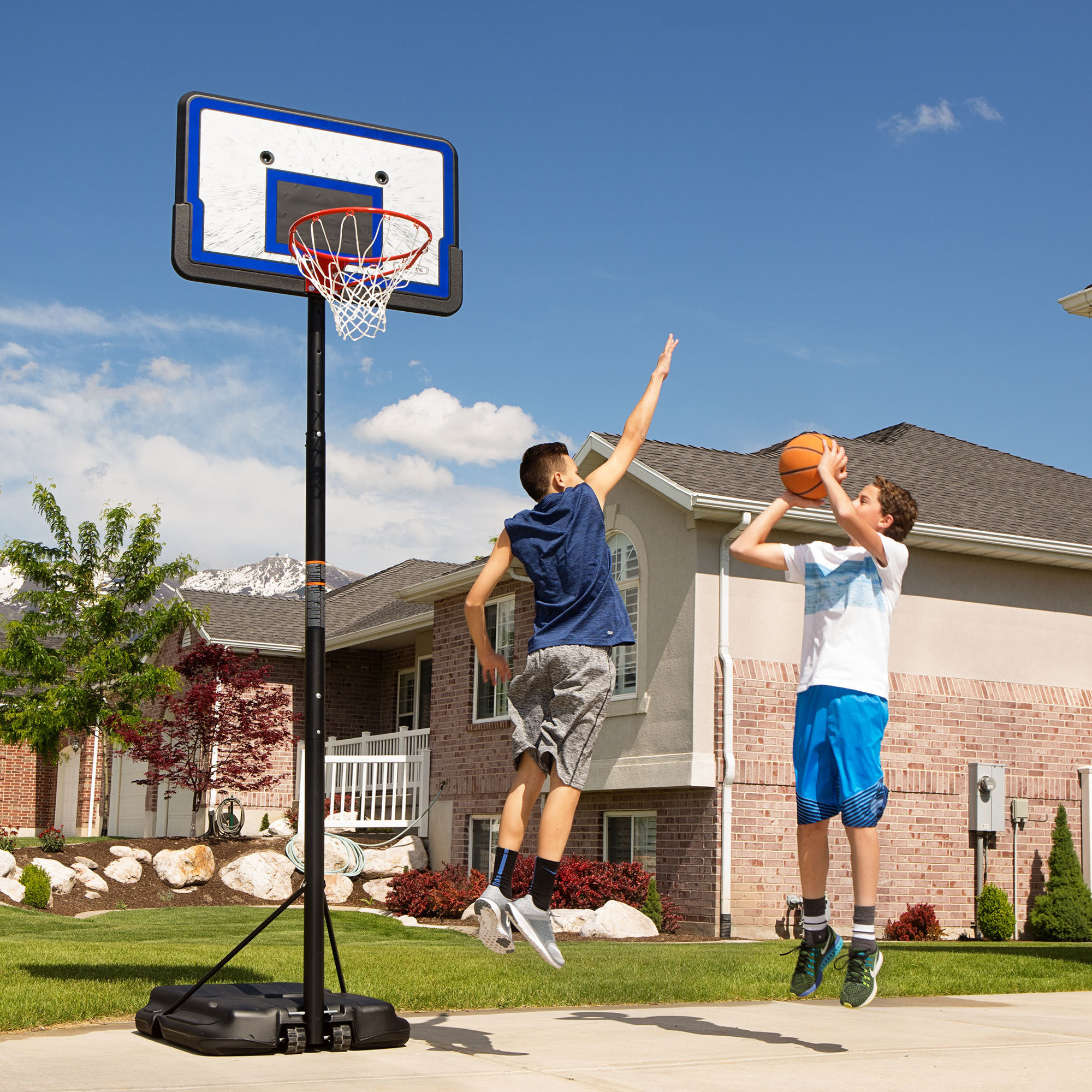 Two players playing basketball with the hoop in front of a house