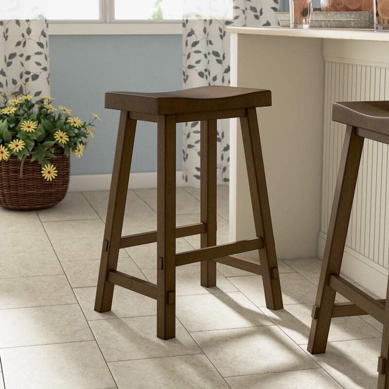 A brown wooden bar stool