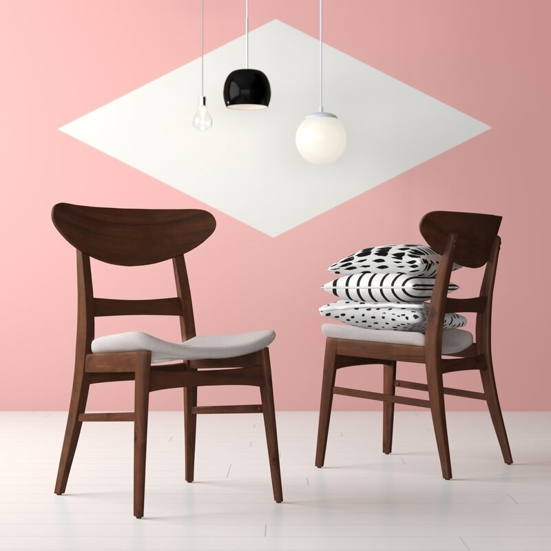 Two brown wooden midcentury modern dining chairs with arched backs