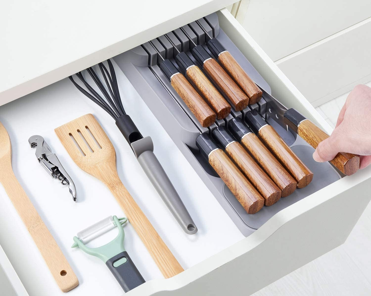 A kitchen drawer full of utensils and the knife organizer