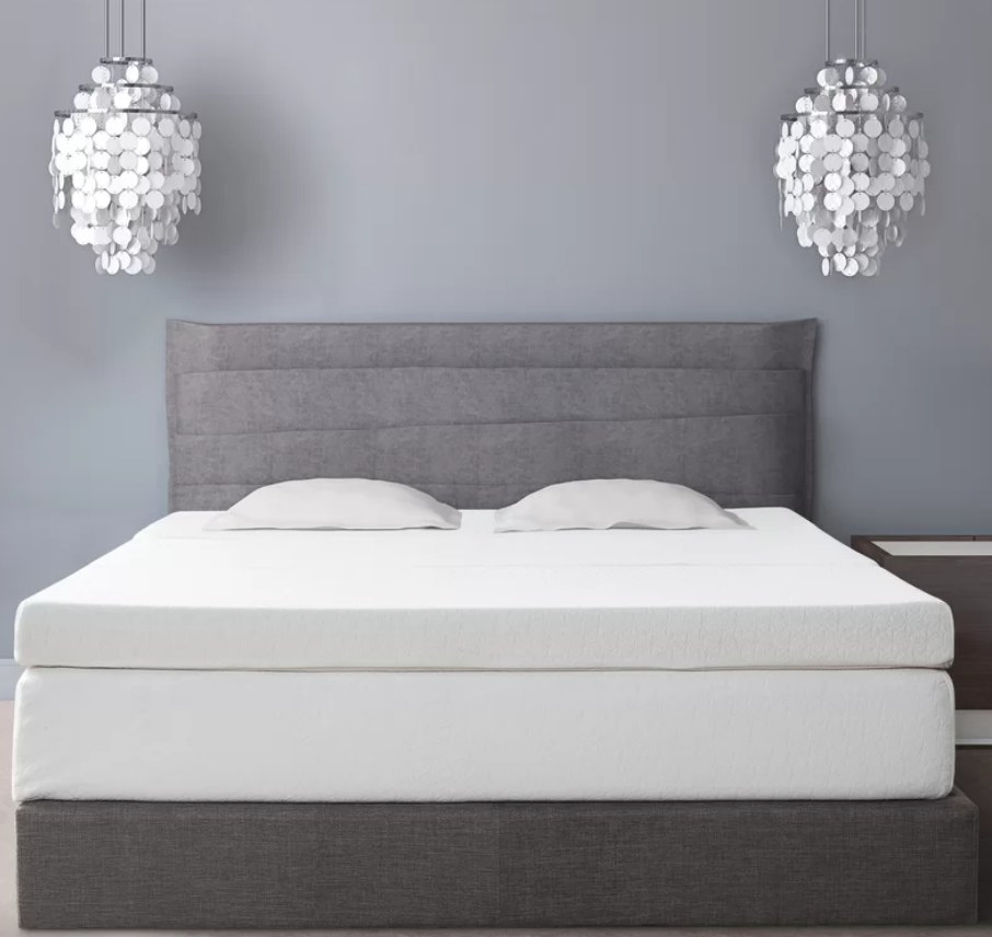 White mattress topper on top of mattress with two white pillows on top, gray bedframe
