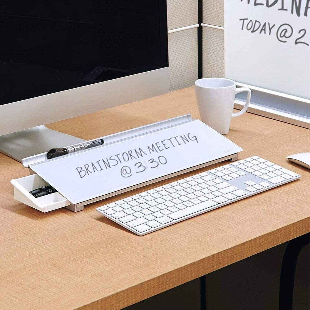 computer and keyboard on a desk with dry erase board