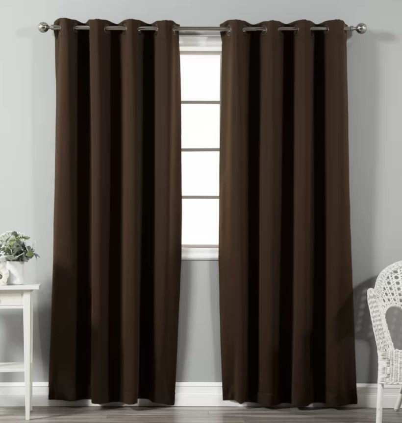 Two long, floor length, brown curtains hanging over window