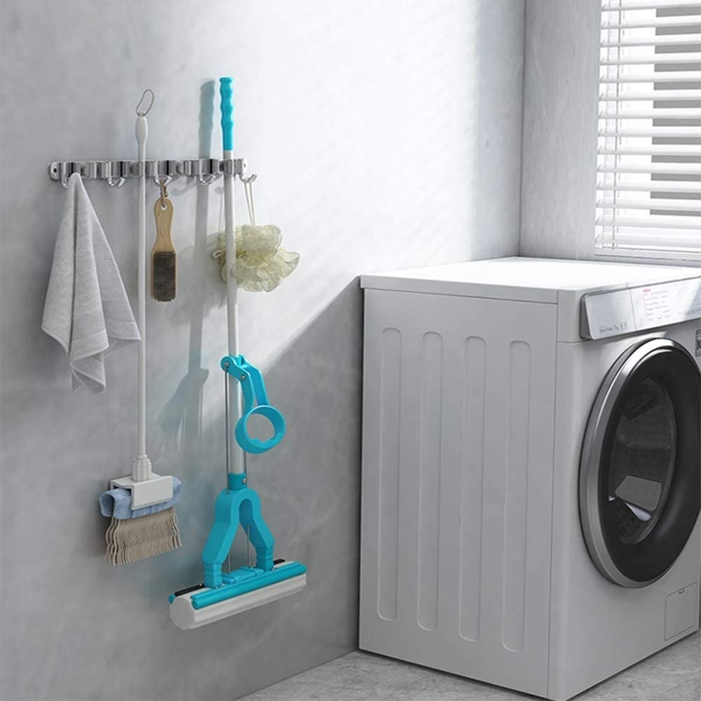 mop and broom holder with different cleaning items next to a washing machine