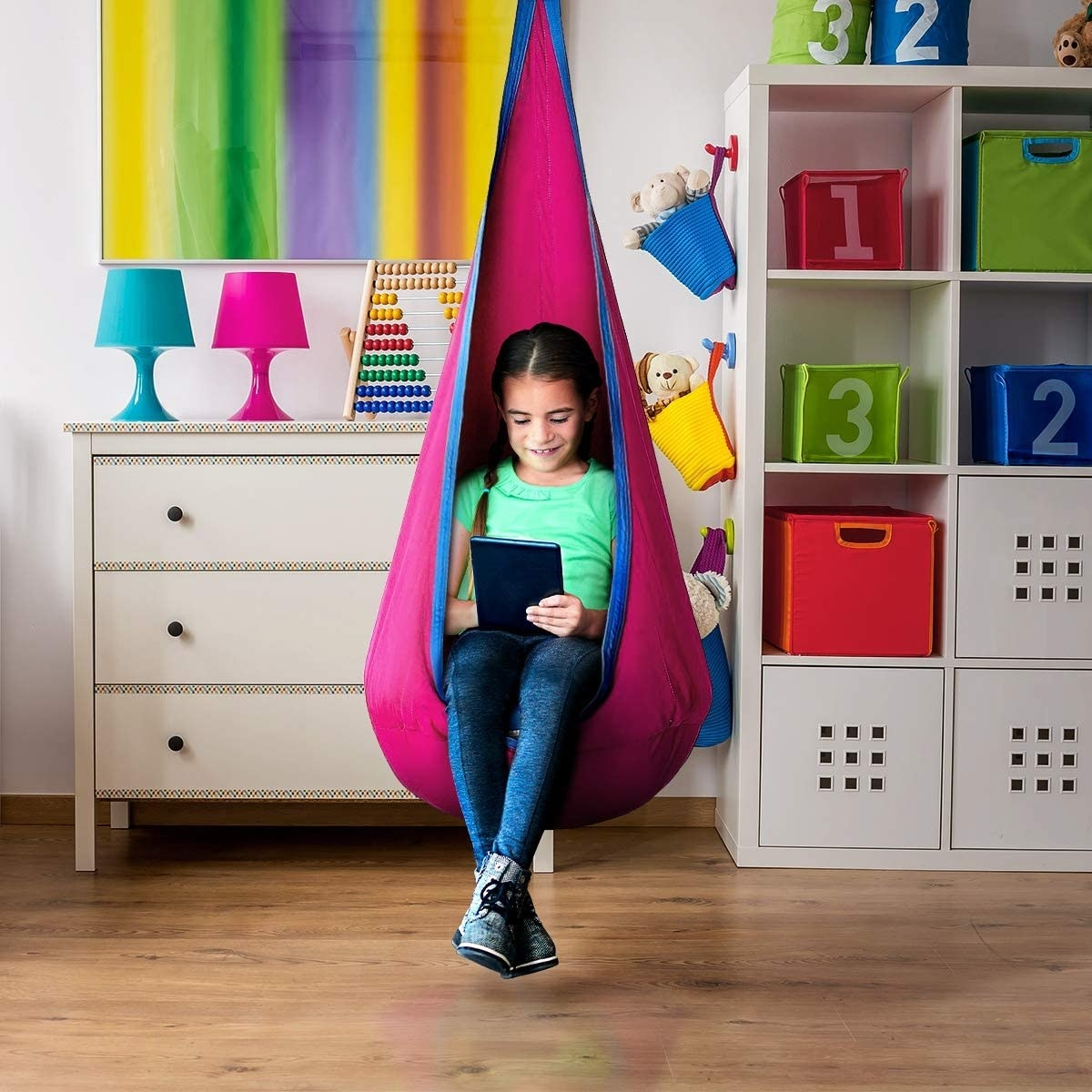 A child sitting inside of the pod in pink and blue