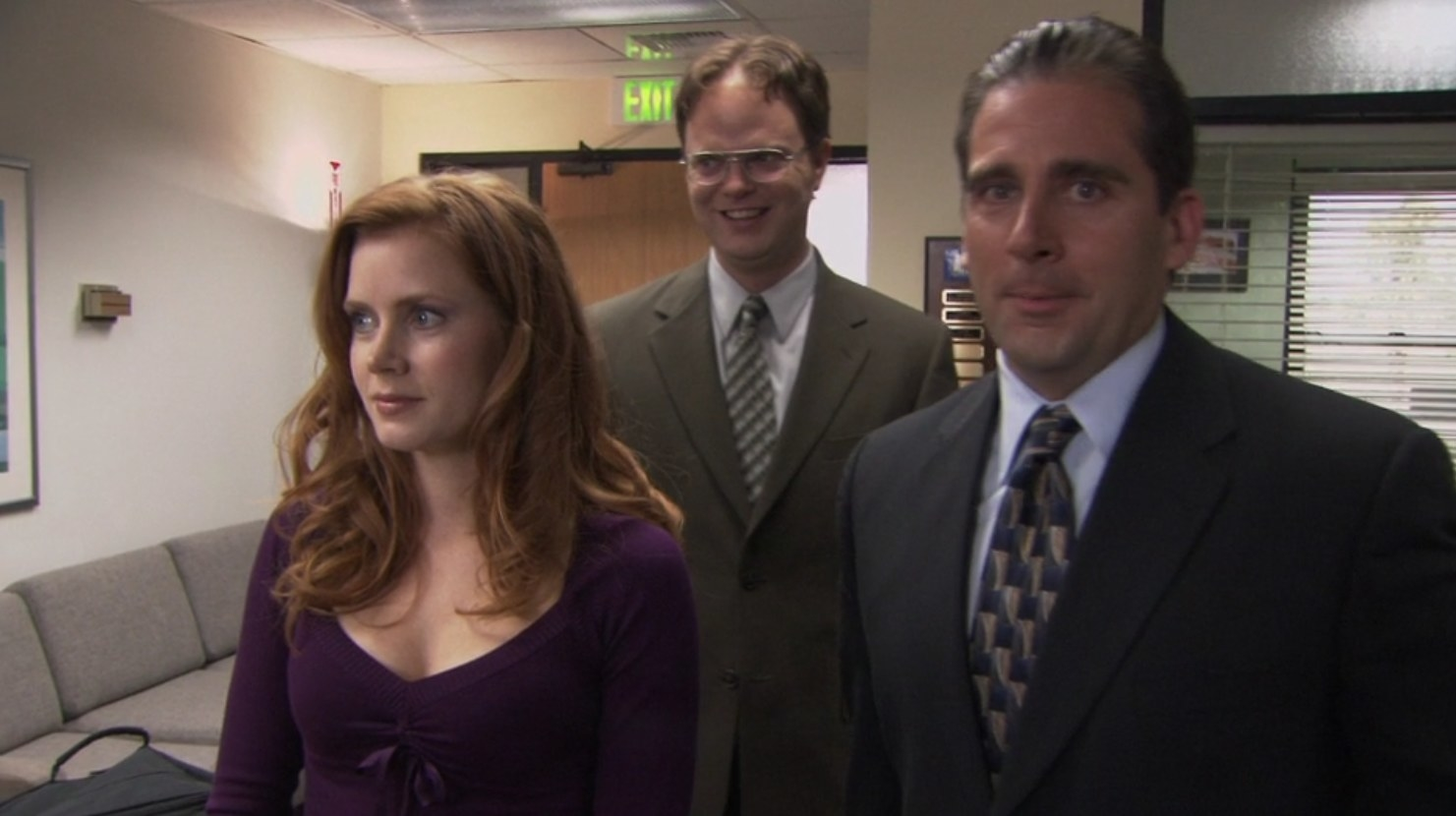 Amy Adams' character Katy stands in front of a smiling Dwight and an awkward Michael