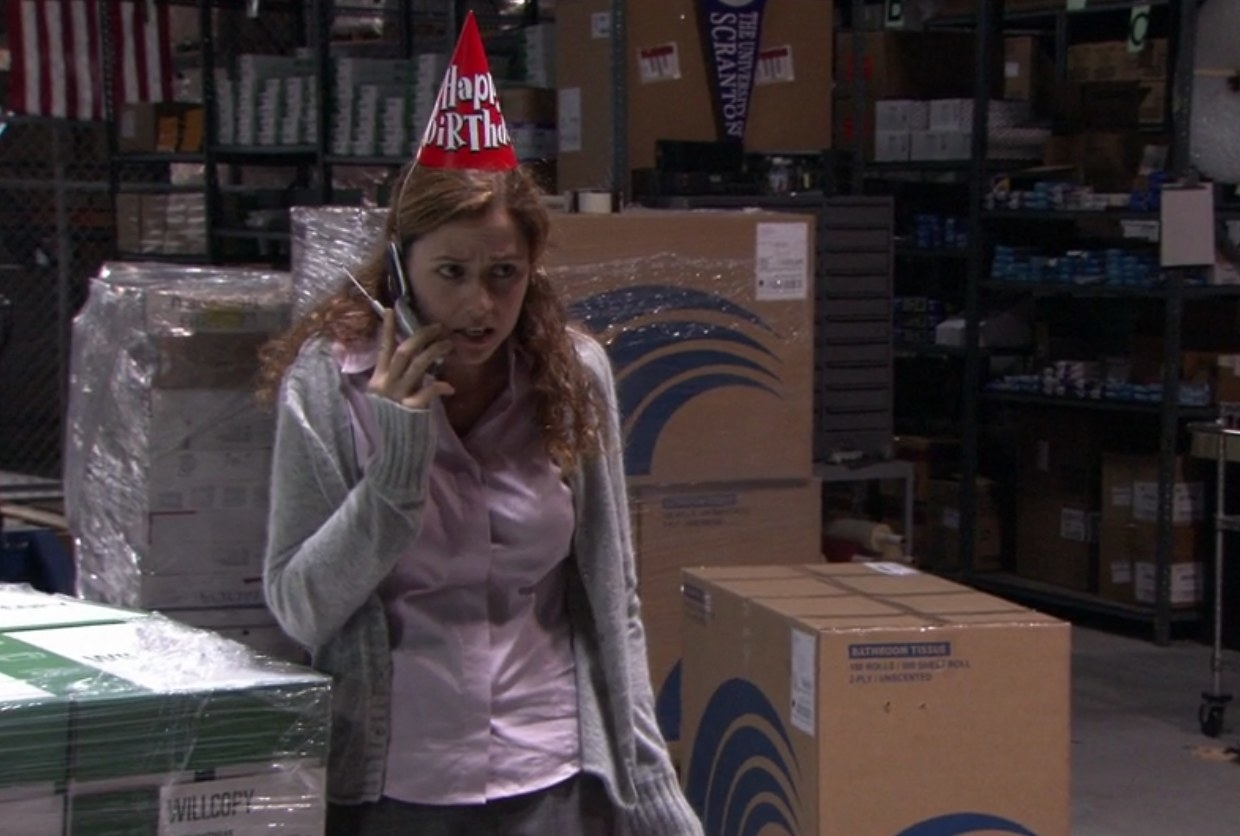 Pam stands in front of a cardboard box in a warehouse, wearing a party hat and talking on the phone