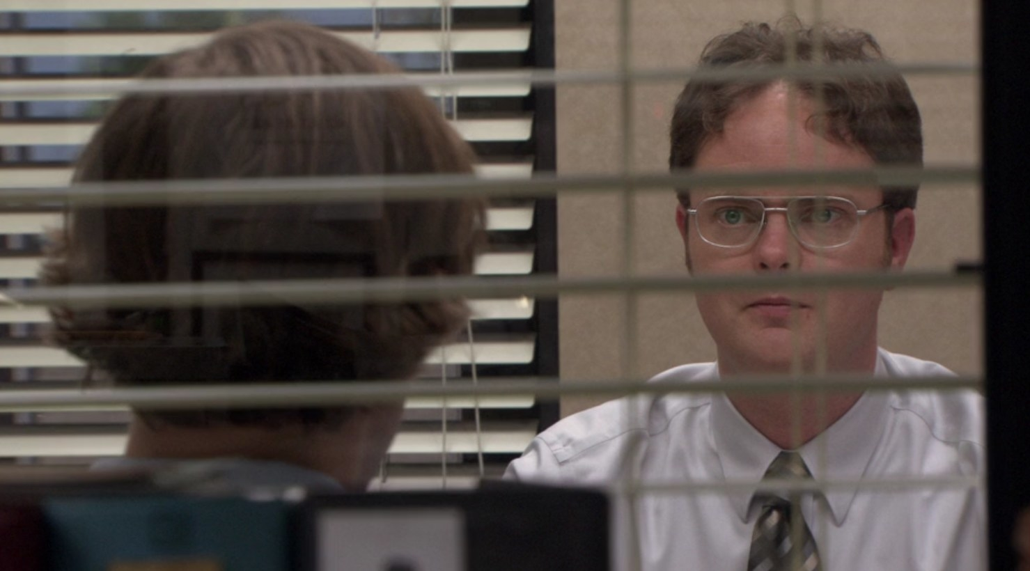 Through a window in the office, we see Jim facing an angry Dwight