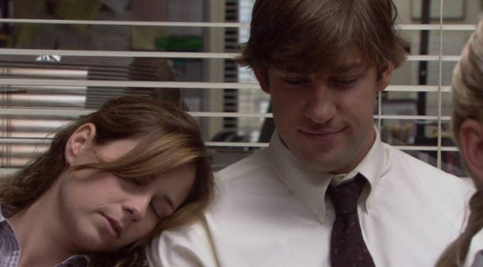 Jim smiles as Pam rests her head on his shoulder, sleeping