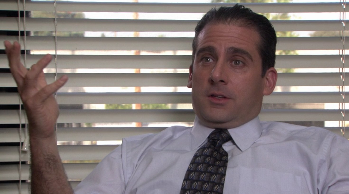 Michael sits in his office, gesturing with his hands as he talks