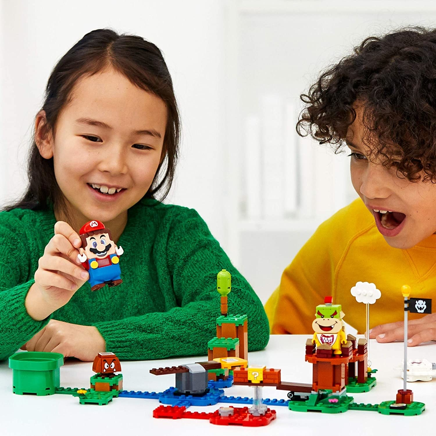 Two children playing with the Super Mario Lego set