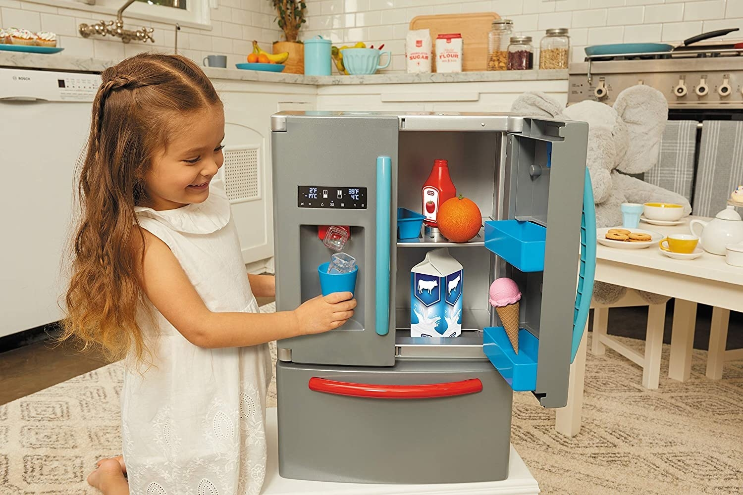 A child playing with the refrigerator playset