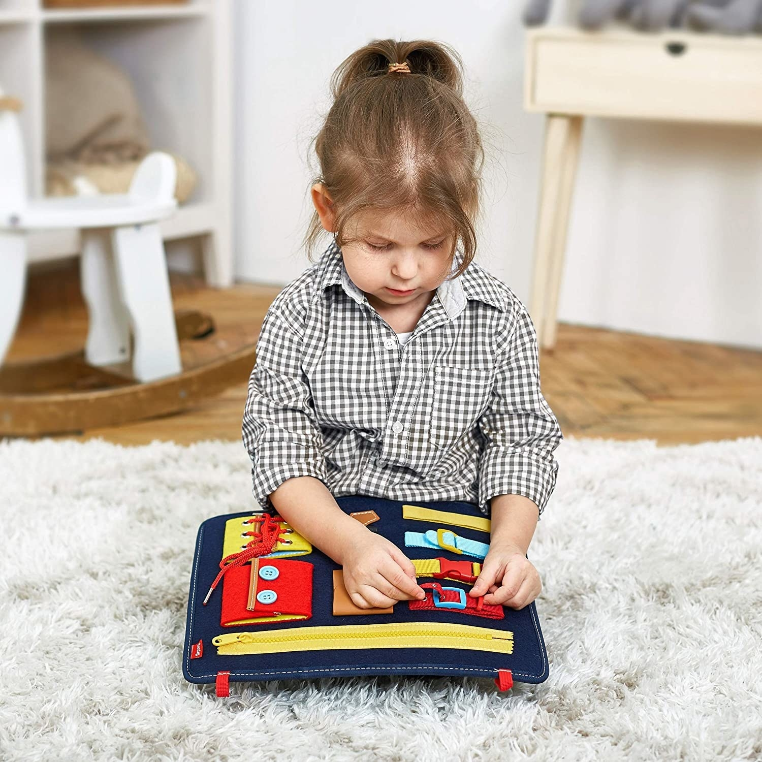 A child playing with the busy board