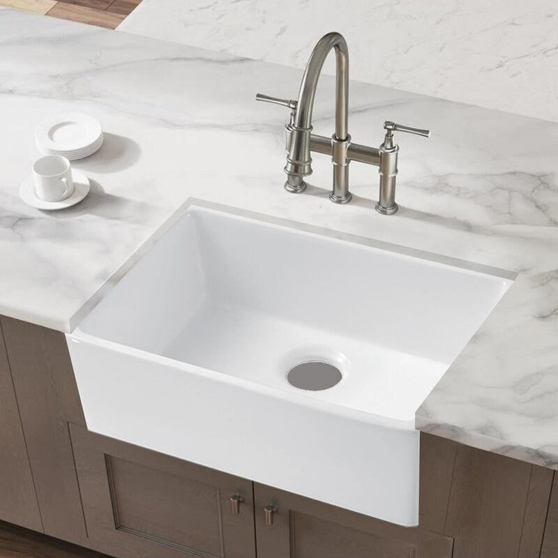 A white farmhouse sink between a marble countertop and brown kitchen cabinets