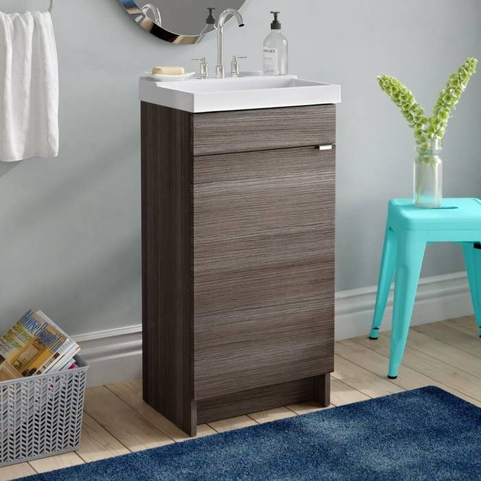 A very slim brown bathroom vanity with a small white sink next to a teal metal stool inside a bathroom
