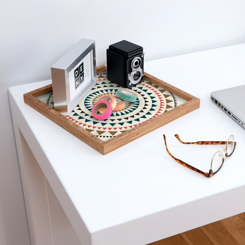 A counter with a geometric tray on it holding a small old school camera, colorful washi tapes and a silver frame