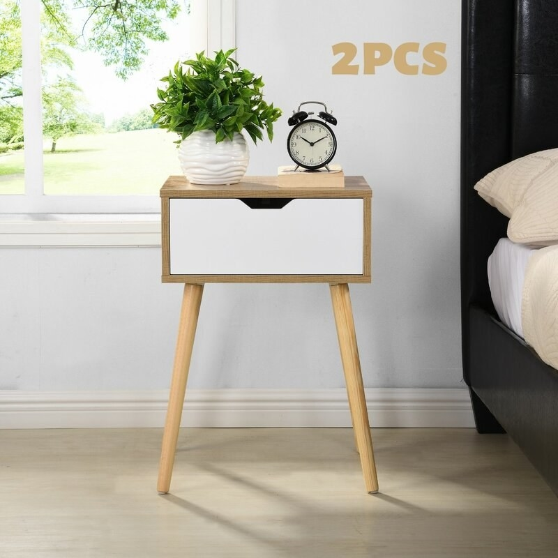 A mid-century modern style side table that's wood with a white drawer next to a black bed frame