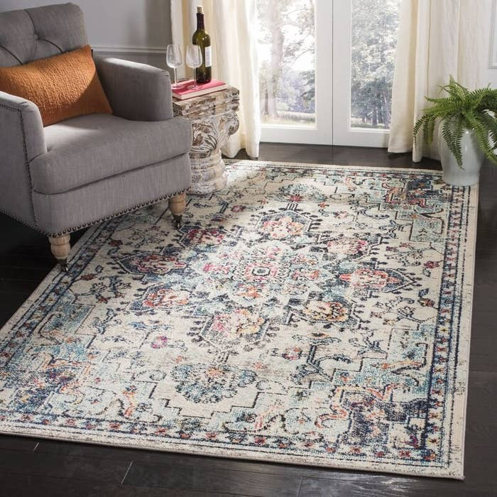 An oriental rug in beige, blue and pink under an accent chair