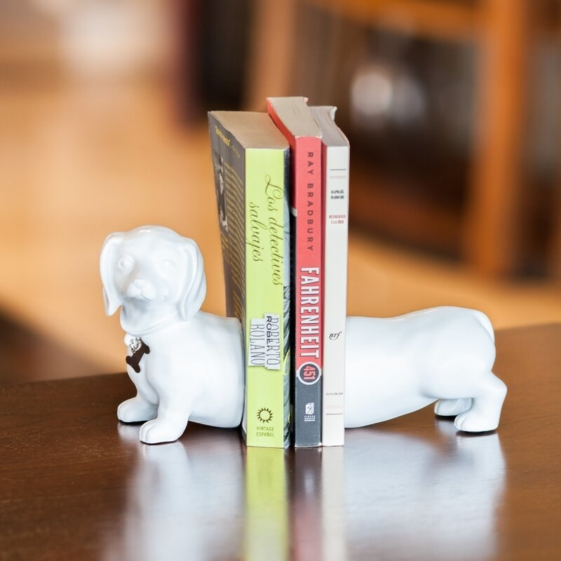 White bookends that look like a dachshund dog with three books in the middle