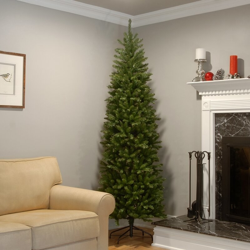 A slim green fake Christmas tree with no ornaments on it inside a family room, next to a couch and fireplace