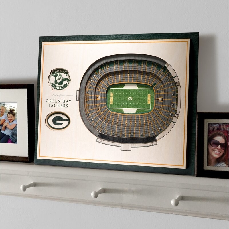 A framed recreation of the Green Bay Packers' NFL stadium on a white shelf next to framed family photos
