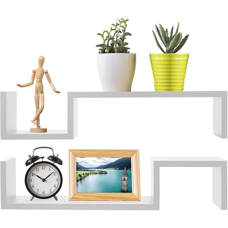 A pair of floating white bookshelves with a clock, a frame, two plants and a wooden figurine