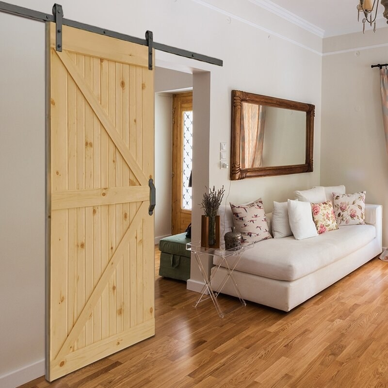 A living room showing a pine wood barn door hanging on a wall next to a chaise lounge and accent mirror