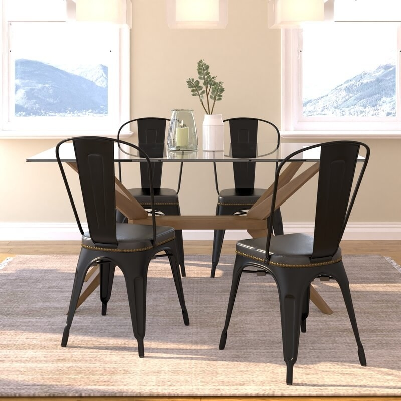A brown dining table over a beige rectangle rug and four black industrial metal chairs with black faux leather seats