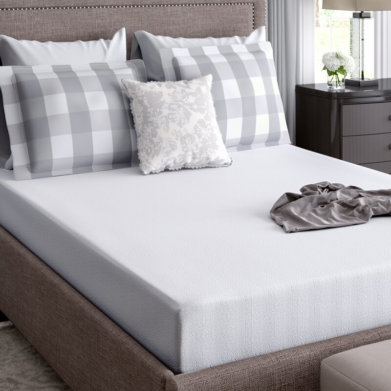 A neatly-made bed with a white mattress and gray and white pillows inside a bedroom