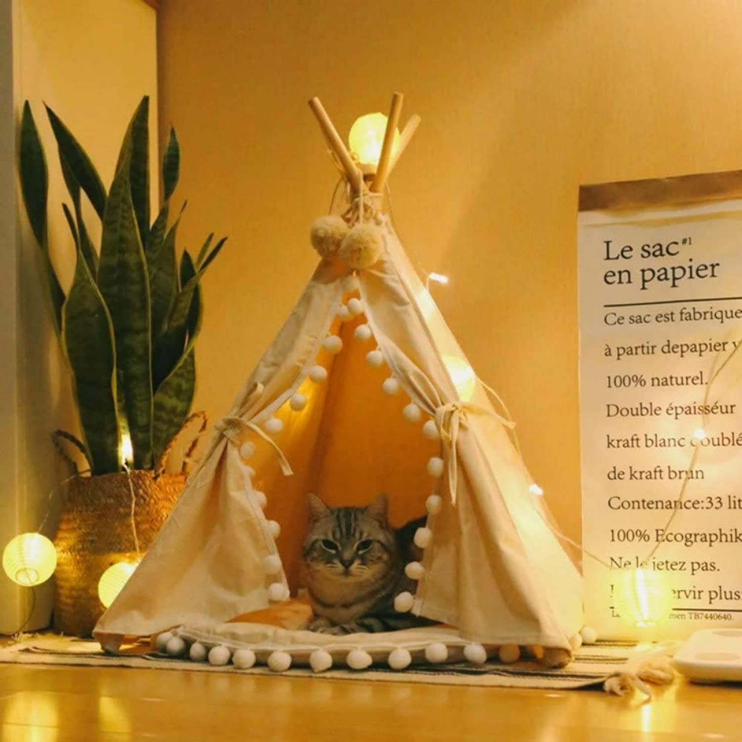 a striped cat sitting inside of a beige cat teepee with pom-poms lining the opening