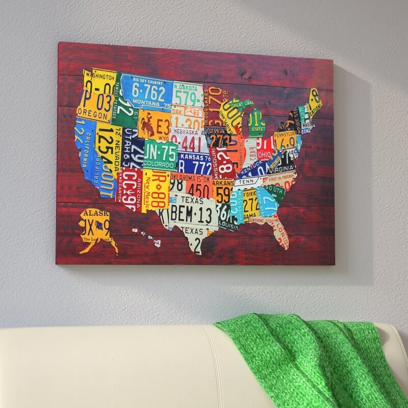 Canvas art work with a red background and a map of the United States on it; each state on the map is in the design and color of that state's license plate