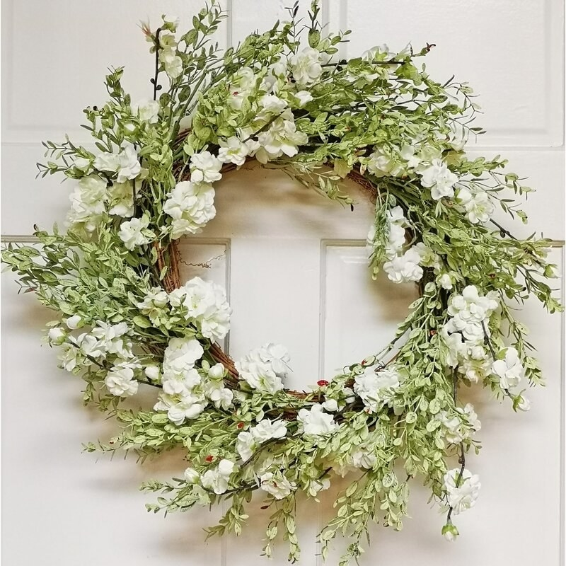 A green and white floral wreath in front of a white door