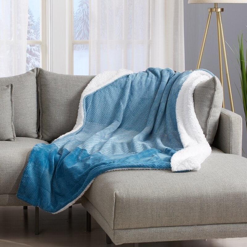 A gray couch with a blue and white velvety throw blanket on it