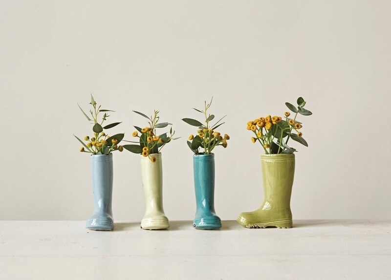 Four ceramic boots in blues and greens with yellow flowers and green leaves in them
