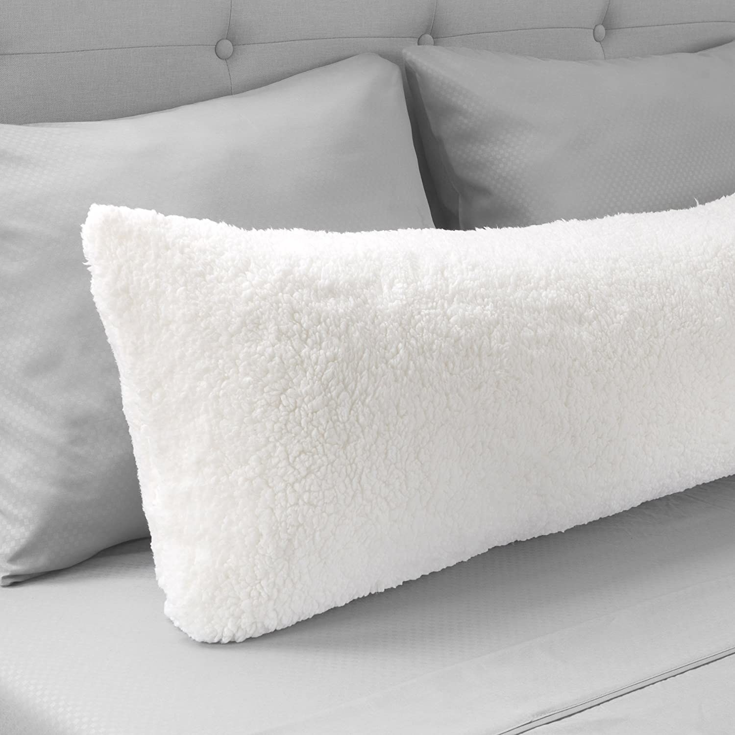 A fluffy body pillow on a bed