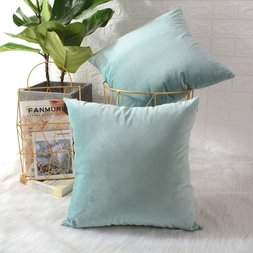 Two decorative pillows One in a small bin and the other leaning against it