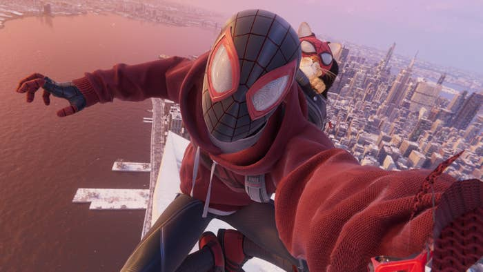 Spider-Man takes a selfie with a cat dressed like him on his back on a rooftop with the skyline of NYC behind him