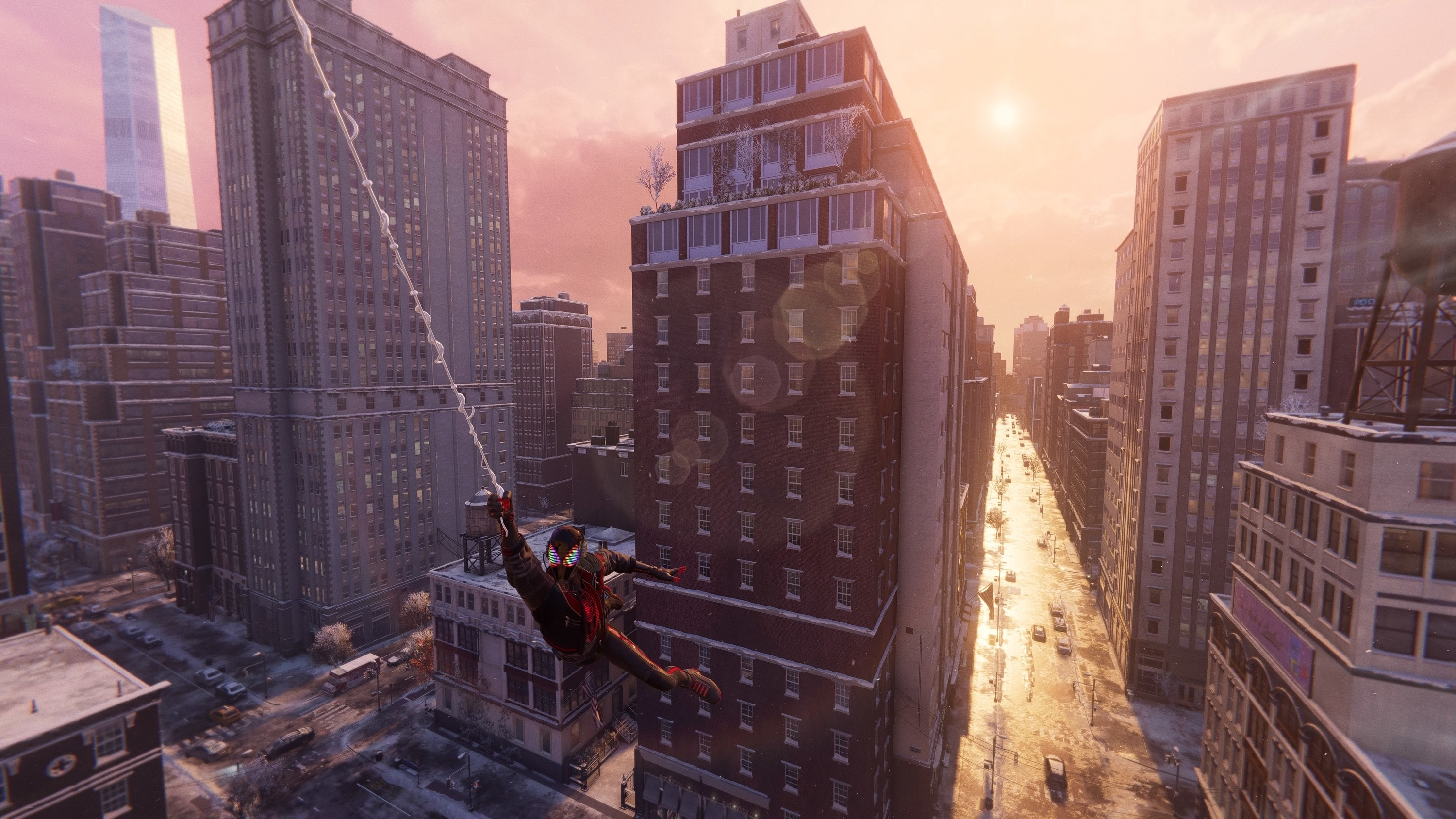 Spider-Man swings on a web through a New York City street as the sun sets behind him