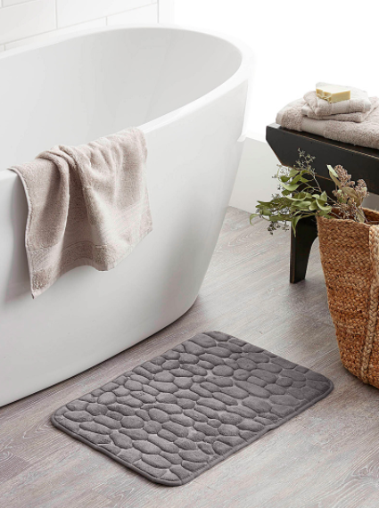 A pebbled bath mat next to a freestanding tub