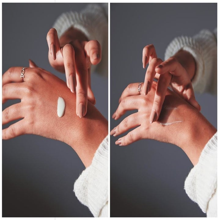 A model rubbing the product into her hand to show it doesn't leave a white cast