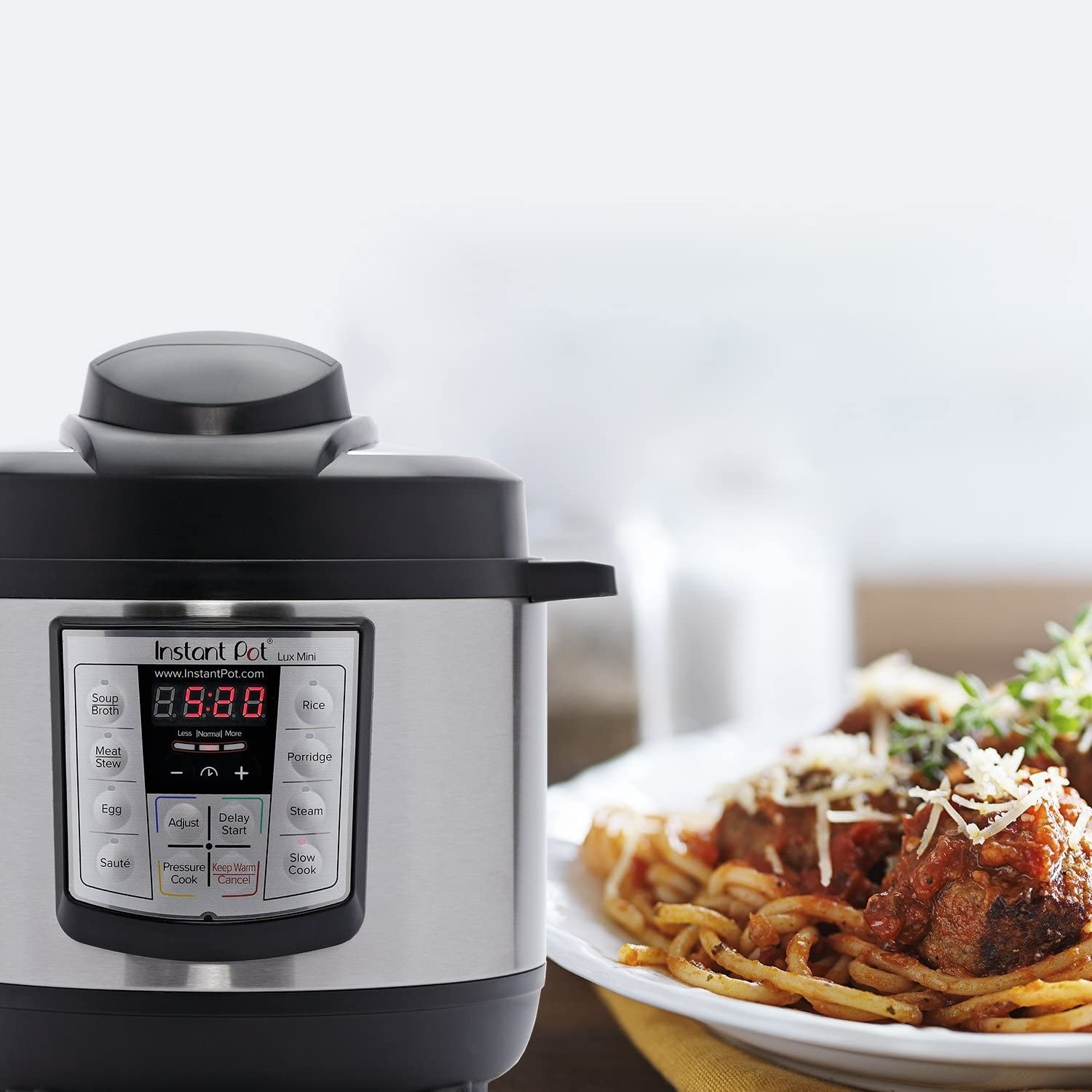 the instant pot lux mini next to a plate of spaghetti and meatballs