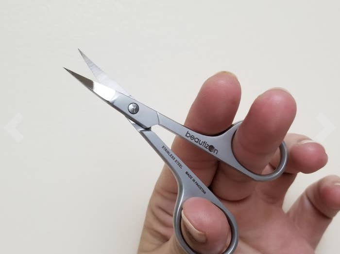 Reviewer holding up tiny stainless steel scissors with curved blades