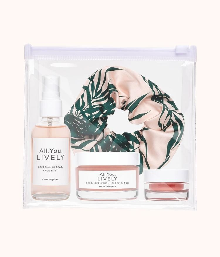 a clear package with a satin scrunchie with a pink leafy print on it, a pink face mist, pink sleep mask, and lip balm
