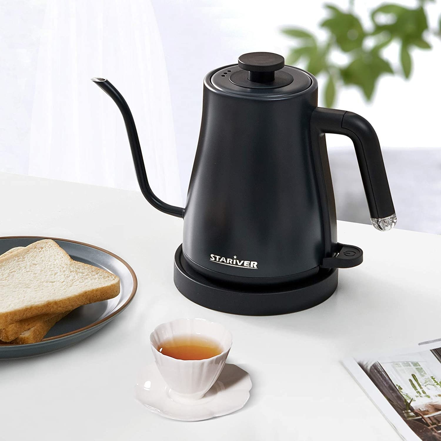 the stariver electric kettle on a breakfast table next to a cup of tea and plate of toast