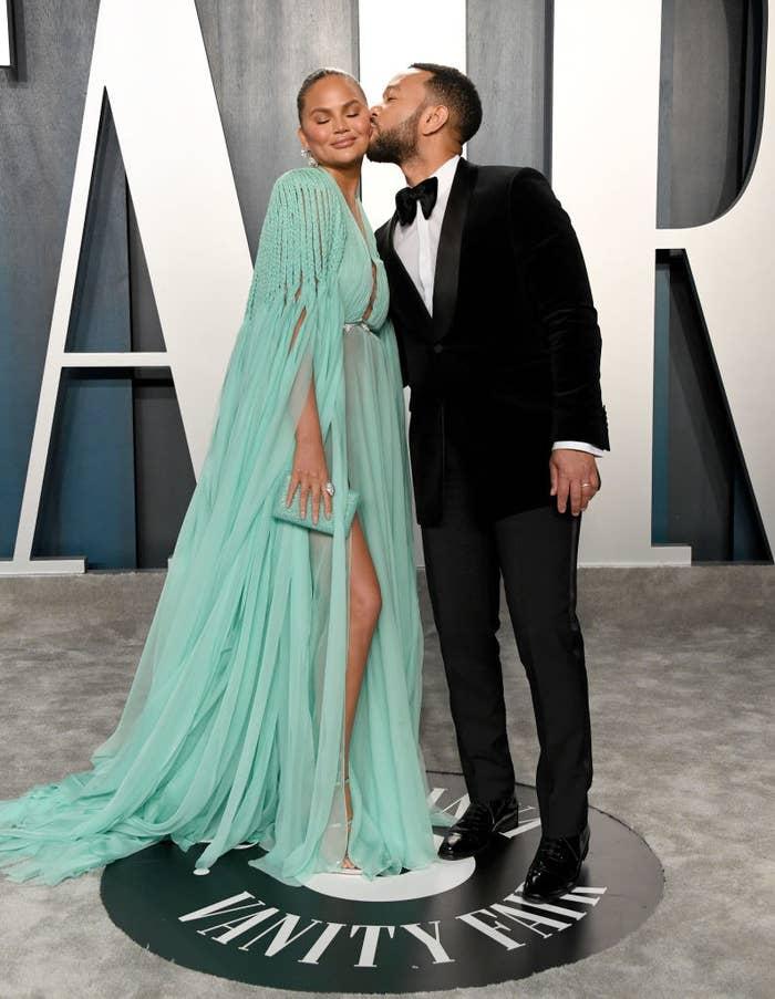 John Legend kissing Chrissy Teigen on the cheek at the 2020 Vanity Fair Oscar Party