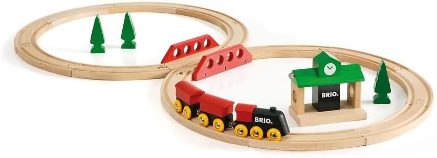 A wooden train set with a track, train, station, and trees
