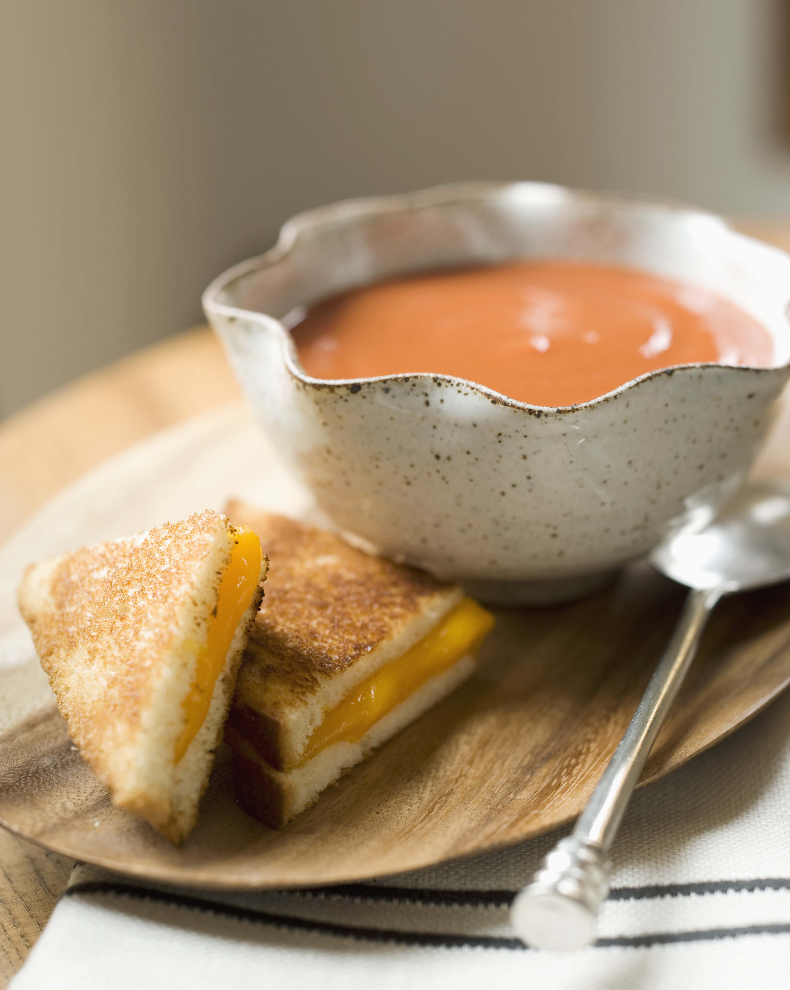 A sliced grilled cheese sandwich and a bowl of creamy tomato soup.