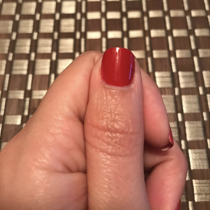 Reviewer with red nail polish on thumb