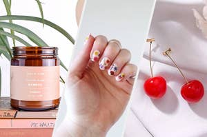 A candle sitting on a stack of books, A person's hand with painted nails that have flower-shaped stickers on them, A pair of drop earrings in the shape of cherries