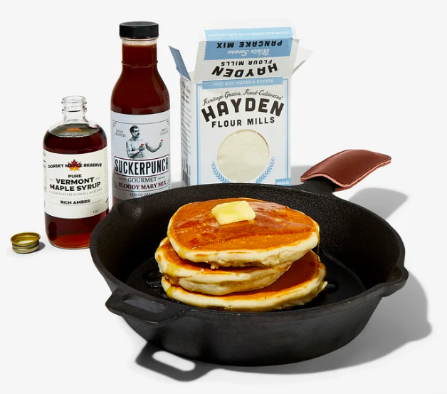 Skillet with stack of pancakes, maple syrup, and bloody Mary mix